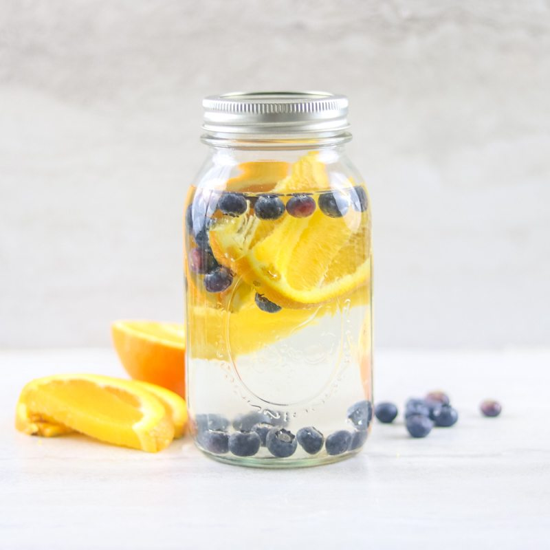 Ball jar filled with water that has orange slices and blueberries in it for Blueberry orange water