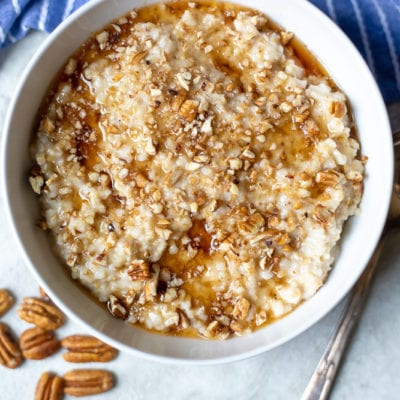 A bowl of creamy crockpot oatmeal in a white bowl topped with pecans and maple syrup