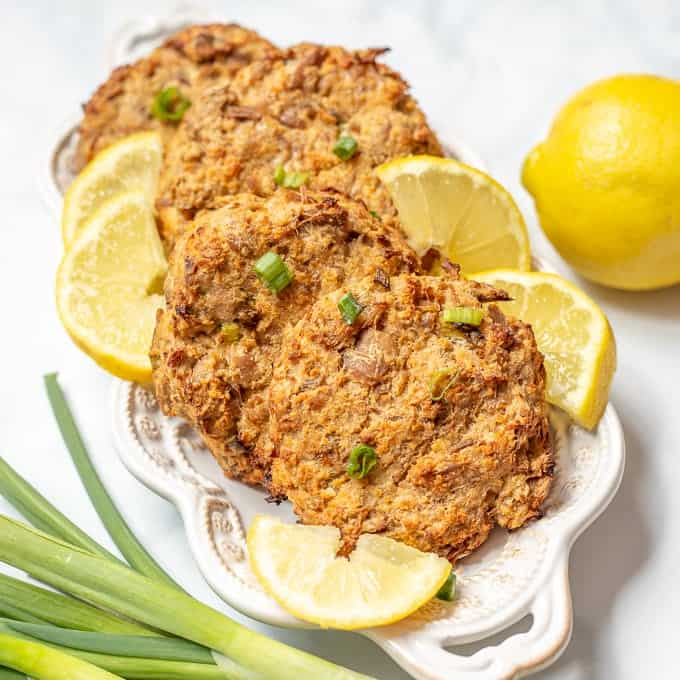 Easy Baked Tuna Patties plated on white plate with lemon wedges