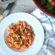 White bowl filled with pasta with red sauce