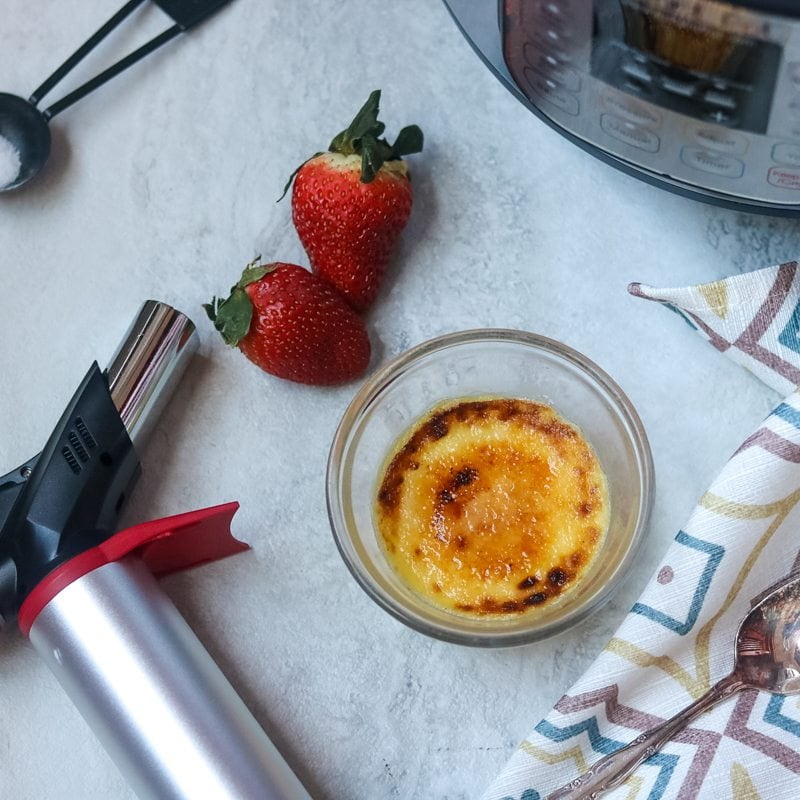 Kitchen torch sitting next to creme brulee with strawberries and instant pot in background