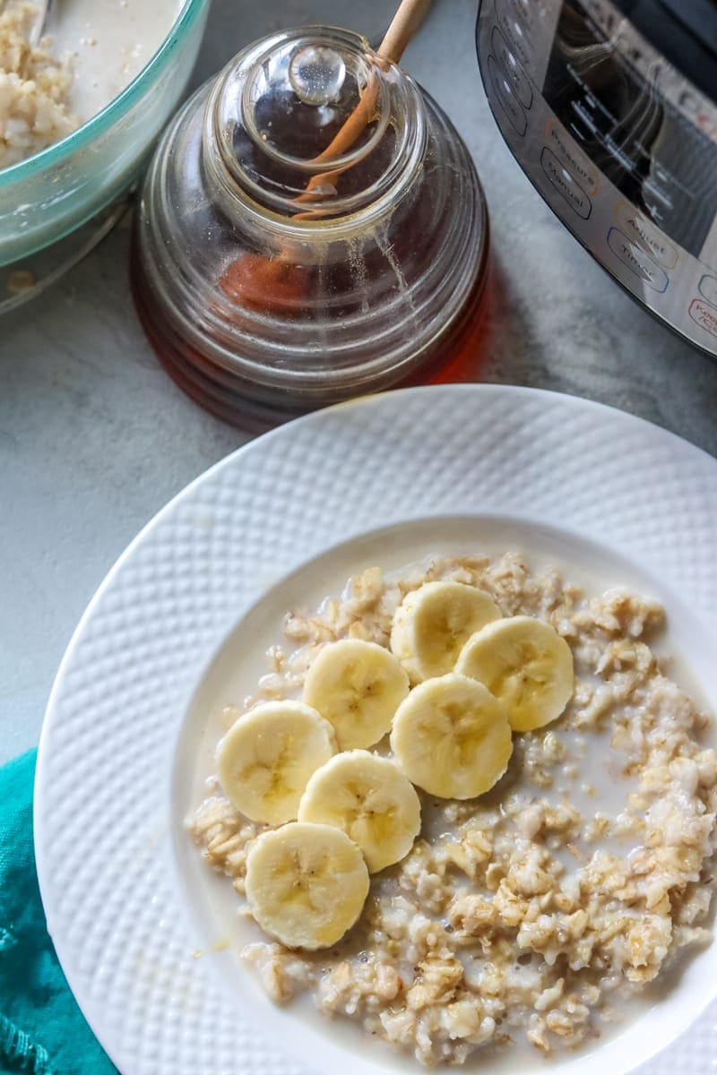 White bowl filled with oatmeal topped with banana next to an instant pot and honey pot