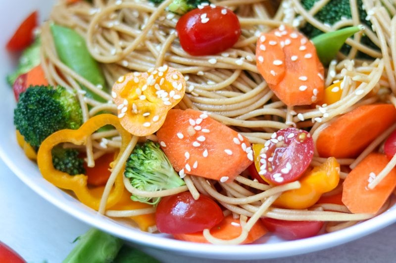 Close up of tossed Asian pasta salad with sliced veggies coated in sesame seeds