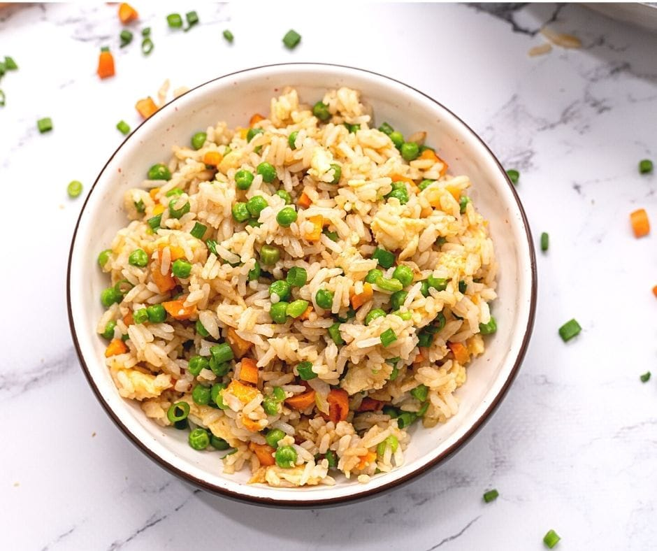 Fried rice made with brown rice and peas in bowl.