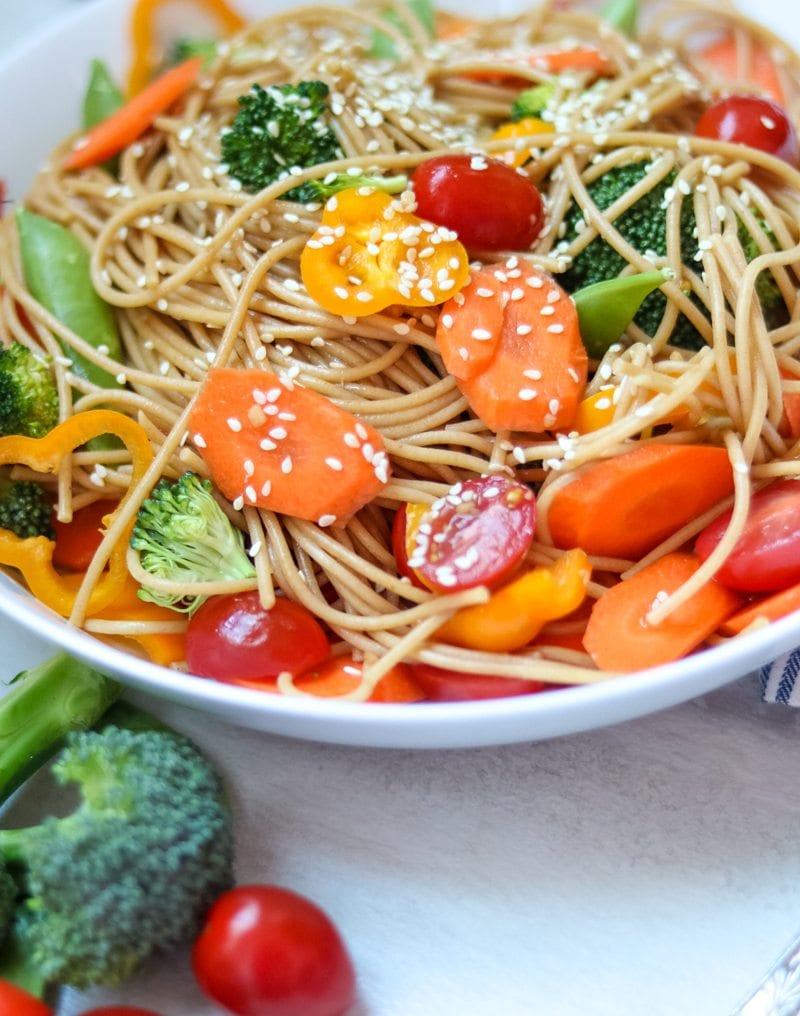 Close up of pasta salad with carrots, peppers, snow peas, tomatoes, broccoli and sesame dressing