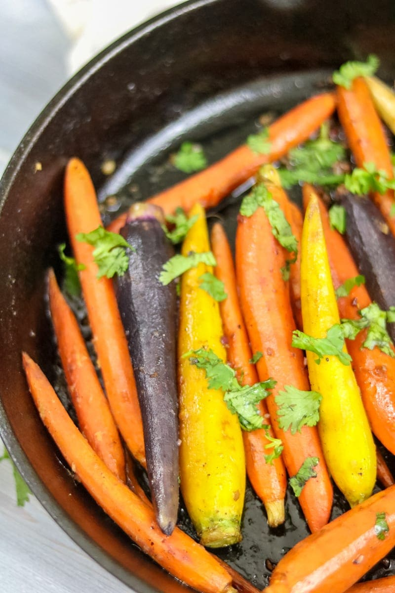 Close up of yellow, purple and orange spring carrots that have been glazed with maple and garlic.