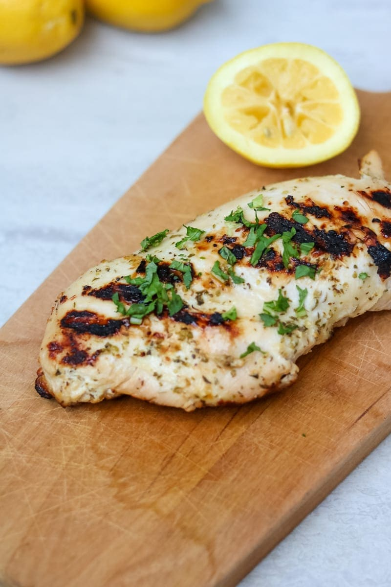 Grilled Greek Yogurt Marninated Chicken Breast on wooden cutting board next to lemons.