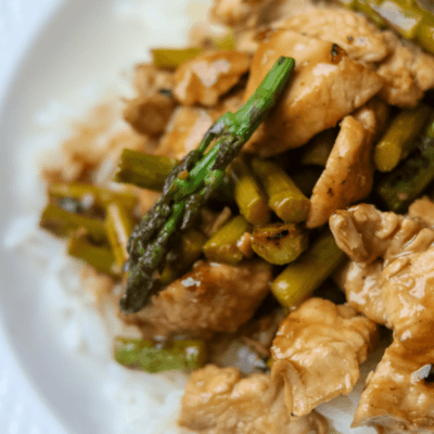 Close up of honey glazed chicken strips with asparagus on bed of rice