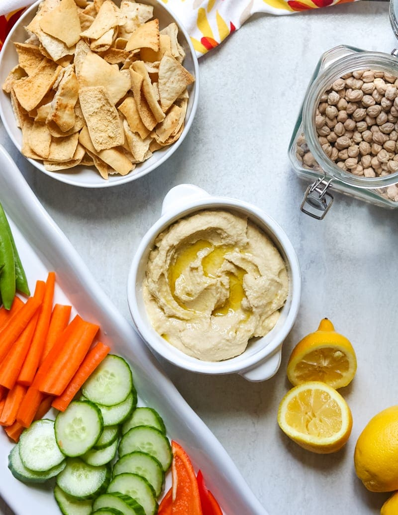 Instant Pot hummus in a bowl next to vegetables and pita chips