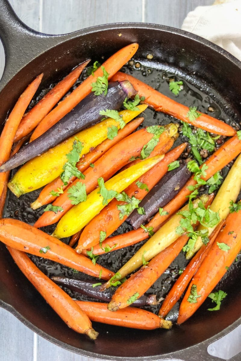 Skillet with jewel carrots that have been pan roasted and glazed