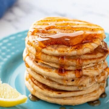Stack of whole wheat pancakes on plute plate topped with syrup