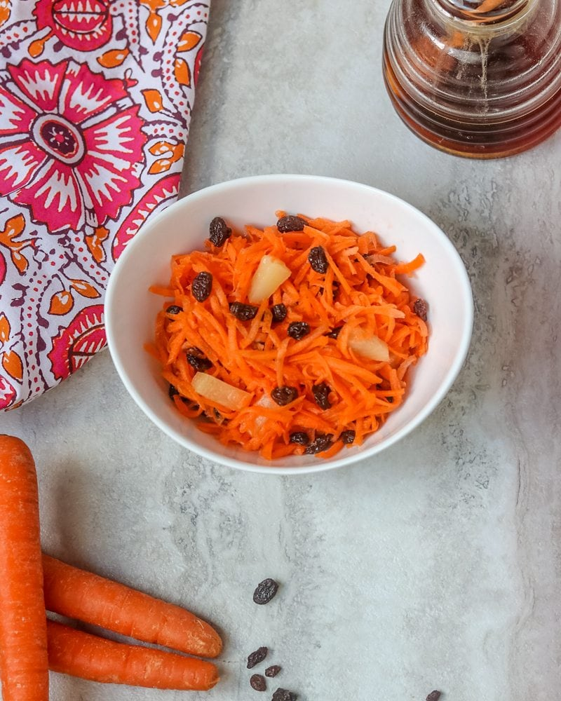 Carrot Salad in white bowl with pineapple and raisins next to a pink and orange napkin on a white counter