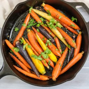 Cast Iron Skillet with golden carrots that have been glazed with garlic and maple syrup.