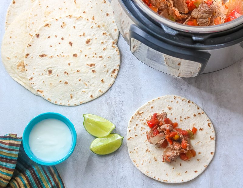 Instant Pot with Steak Fajitas on the side.