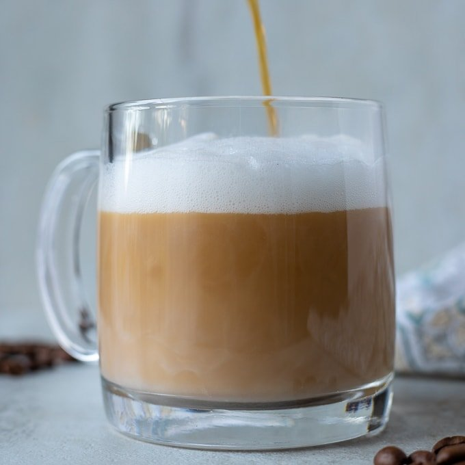 Coffee being poured into a mug with frothed milk