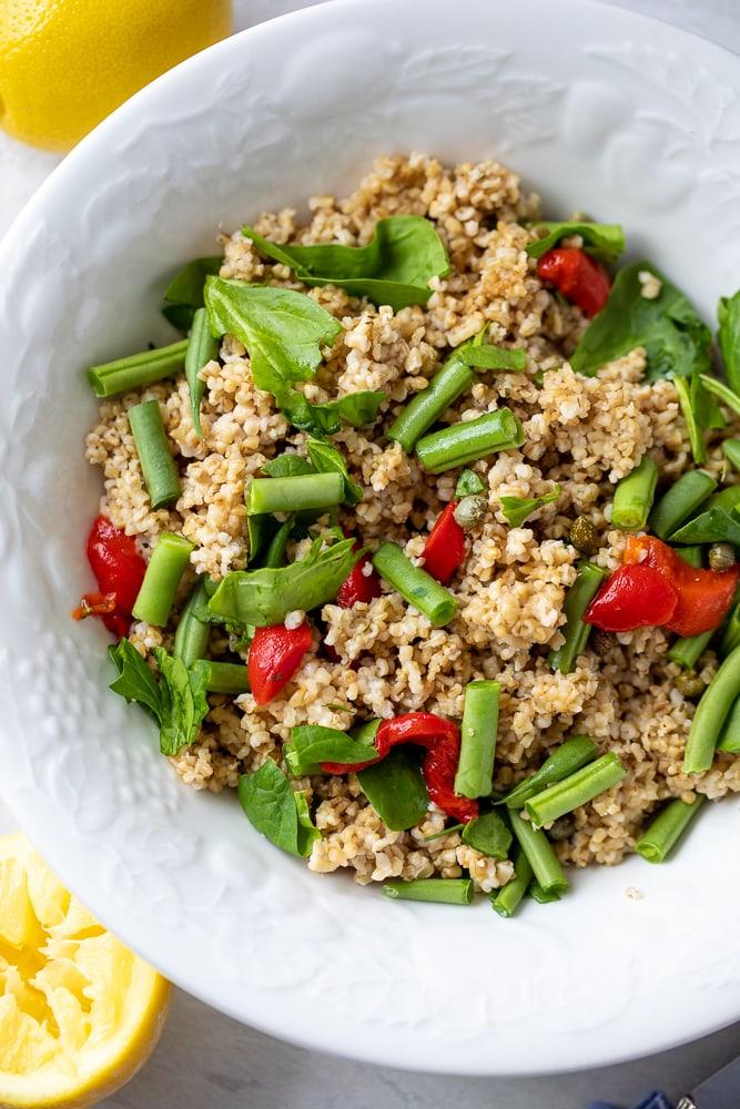 Bowl of Spinach Quinoa Salad next to lemons