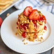 Peanut Butter Pancakes stacked on white plate with strawberry sauce and peanut butter