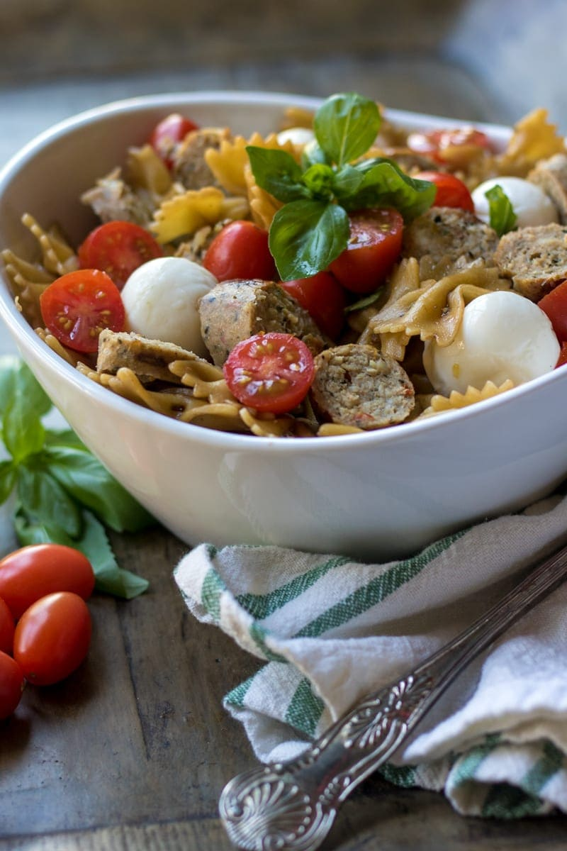 Bowl of bowl tie pasta salad made with tomatoes, mozzarella, balsamic dressing and basil.