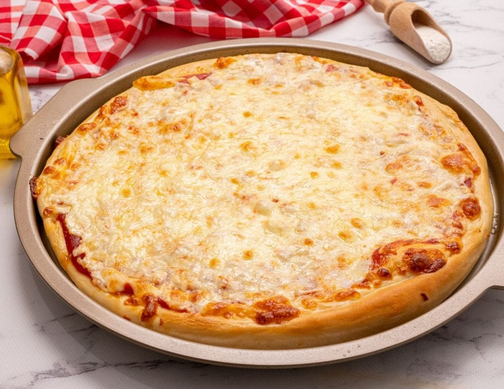 Cheese pizza made with homemade pizza dough on pizza pan