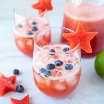 2 glasses of watermelon sangrias with blueberries and watermelon stars