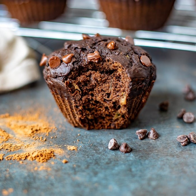 Chocolate Zucchini Muffin with bite out of it next to chocolate chips and cocoa powder