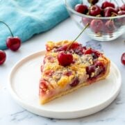 Slice of Cherry Pie on White Plate with fresh cherry on top