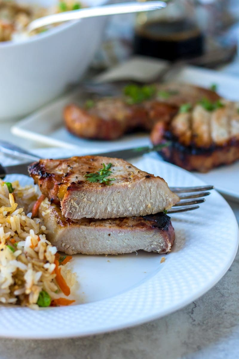 A boneless Honey Garlic Pork Chop served with easy fried rice.