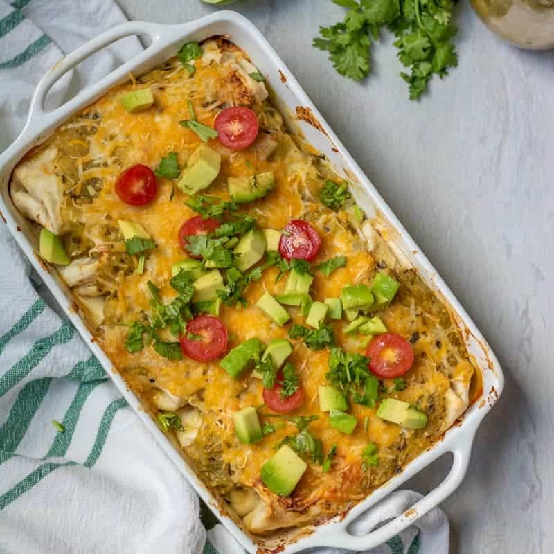 Baked Chicken Enchiladas topped with avocado, tomatoes, and cilantro