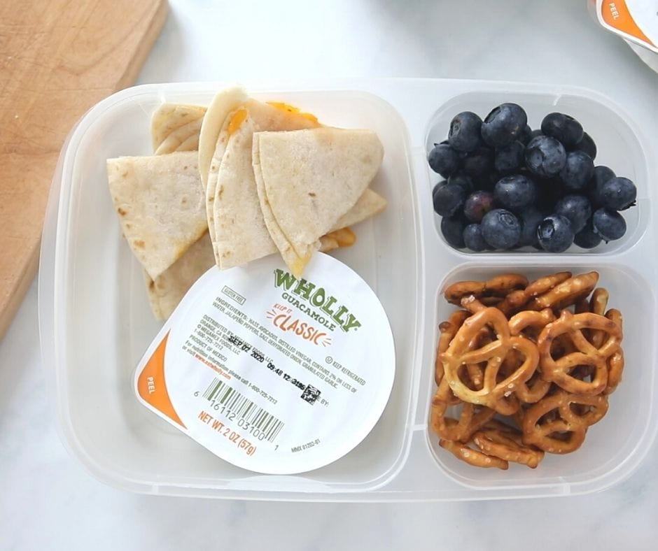 Cheese Quesadilla, guacamole, blueberries, and pretzels in lunch container