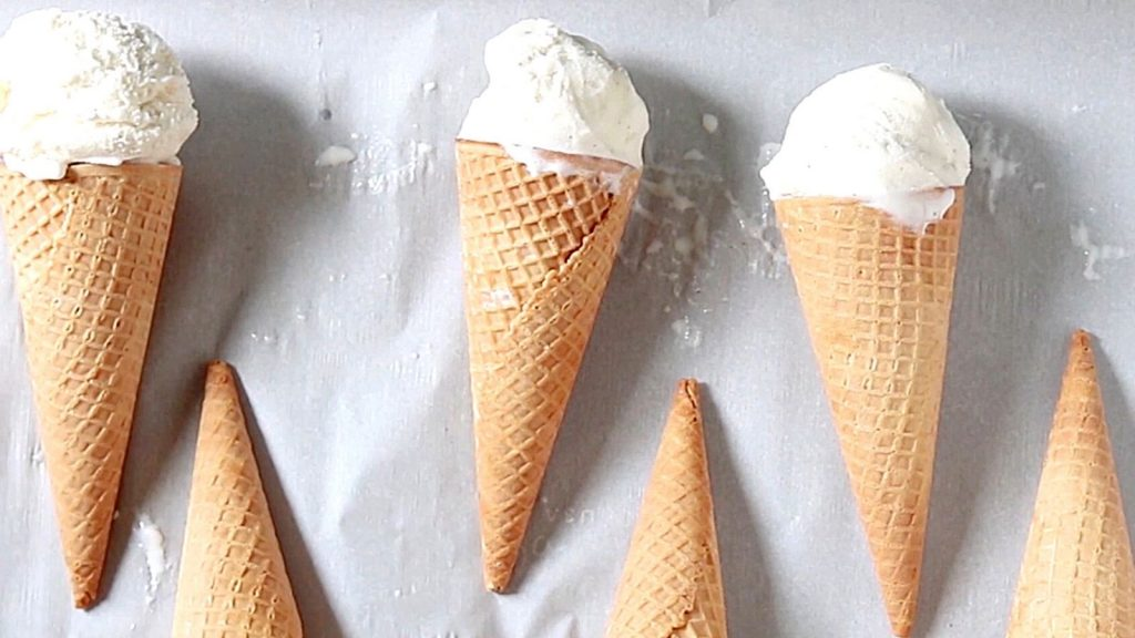 Ice cream Cones with vanilla ice cream on parchment paper lined tray