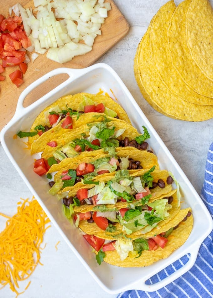 Baked Black Bean Tacos in white dish next to toppings