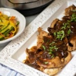 Instant Pot Chicken Marsala on platter next to vegetable saute