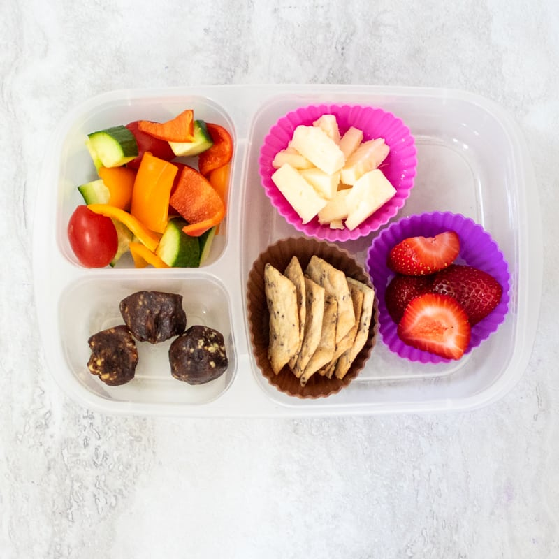 Crackers, cheese, strawberries and veggies in lunchbox