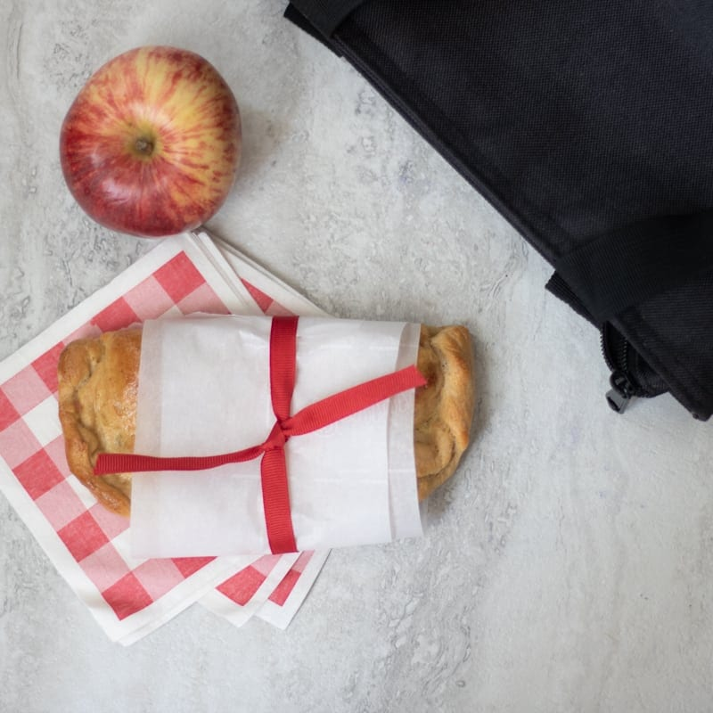Ham and Cheese Hot Sandwich wrapped up in parchment paper with apple
