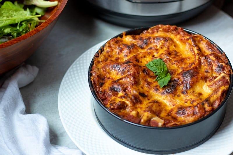 Baked Instant Pot Lasagna in pan next to salad.
