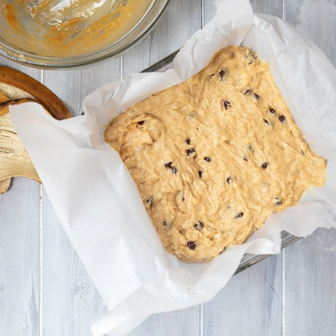 Banana Bar batter in 8x8 baking dish lined with parchment paper