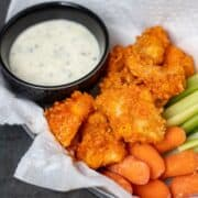 Boneless wings with ranch dressing and celery in basket