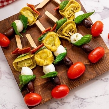 Antipasto Skewers with tomatoes and mozzarella on wooden cutting board ready to be served.