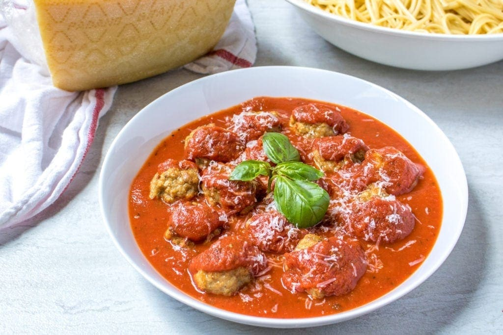 Baked Italian Chicken Meatballs in white bowl with tomato sauce and paremesan cheese .