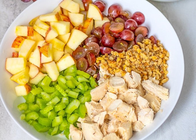 Ingredients for Waldorf Chicken Salad in white bowl.