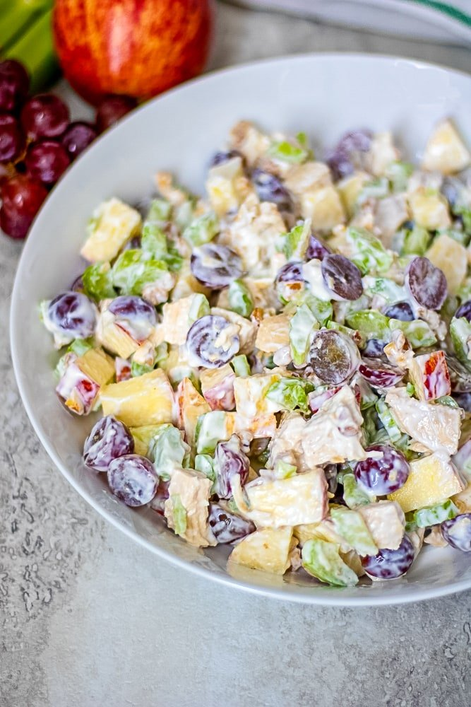 Waldorf Chicken Salad mixed together in white bowl next to apples and grapes