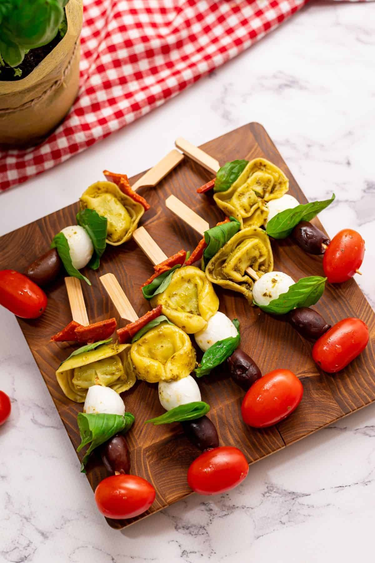 Appetizer sticks with cherry tomatoes, tortellini, basil, mozzarella and pepperoni on wooden cutting board.