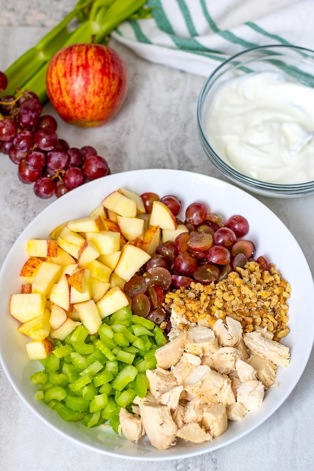 Chicken Salad with celery, apples, walnuts, and apples in white bowl