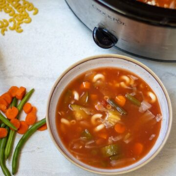 Bowl of Minestrone Soup next to Slow Cooker