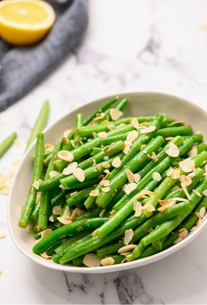 Green Beans Almondine dished out in white dish