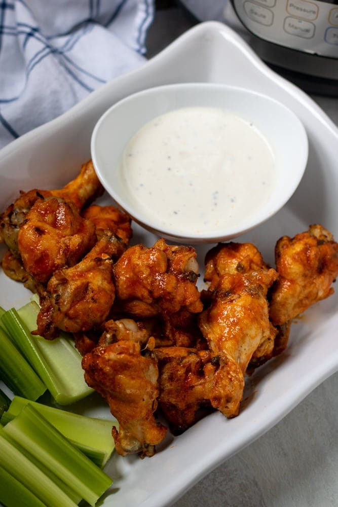 Buffalo Chicken Wings piled on a white platter served with ranch and celery next to pressure cooker