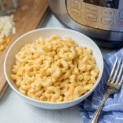 Bowl of Creamy Macaroni and Cheese next to Instant Pot