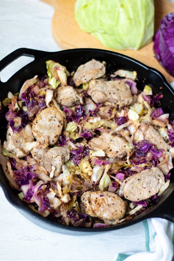 Cast Iron t with Pork Tenderloin Pork Chops and cabbage next to cabbage