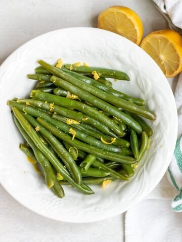 Steamed Green Beans in White Bowl with lemon zest