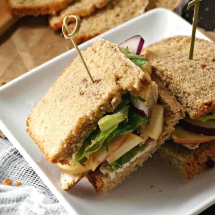 Turkey Sandwich with White Cheddar and Apples sliced open and served on white plate